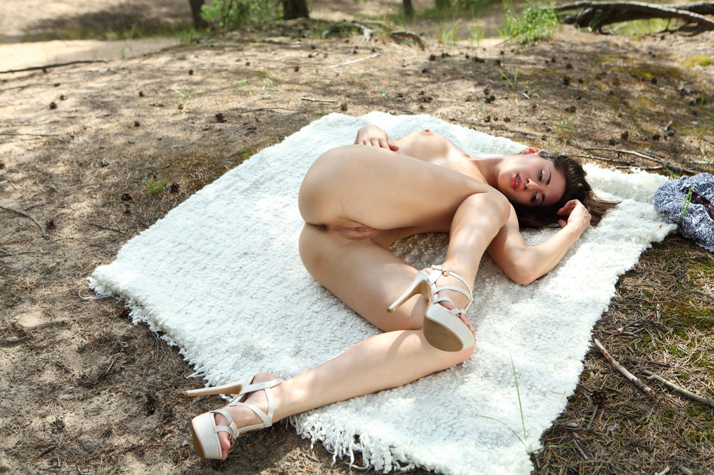 Assoli playfully lifts the hem of her dress, revealing her shapely thighs and a gorgeous, meaty pussy