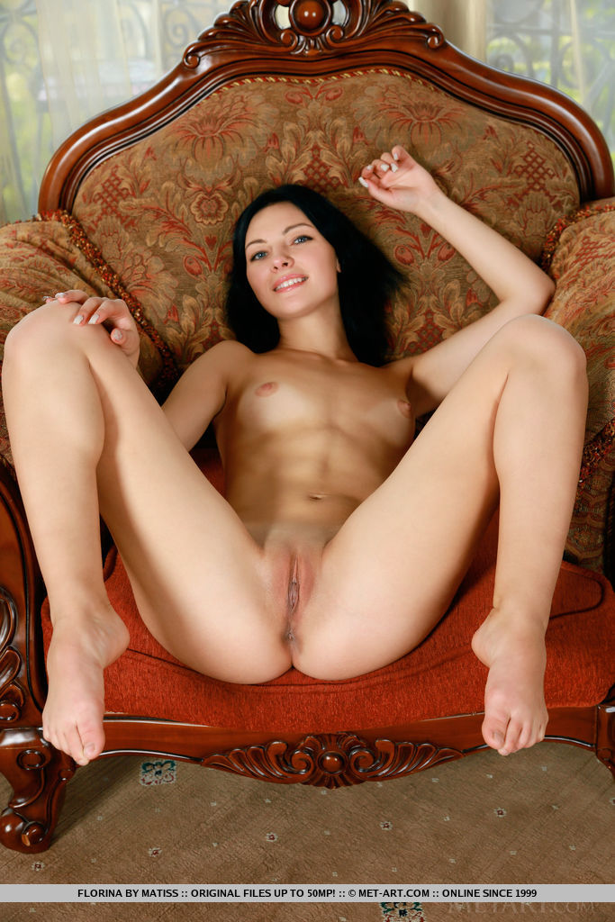 Florina strips by the window baring her shaved pussy.