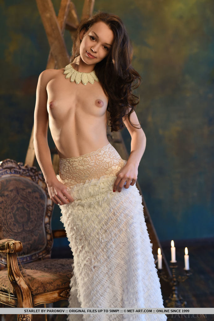 Starlet strips her white long gown baring her tight sexy body, yummy ass and smooth pussy as she pose on the chair.