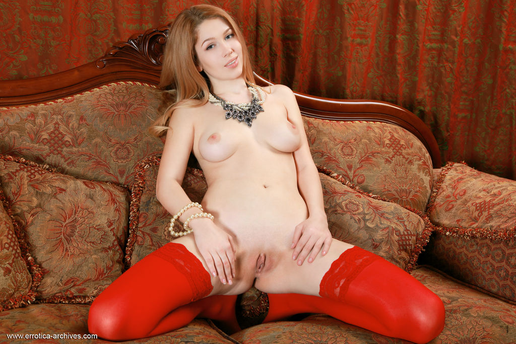 Genevieve Gandi displays her sexy, red stockings baring her sweet pussy.