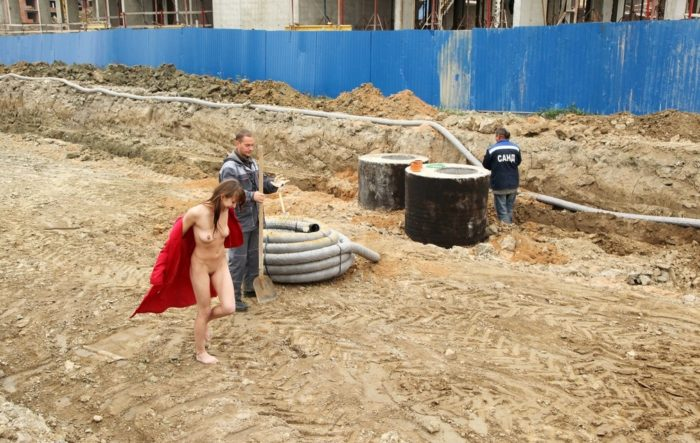 A girl without clothes helps workers at a construction site