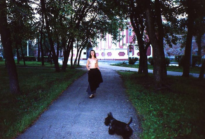 A girl without clothes walks a dog in the morning Moscow