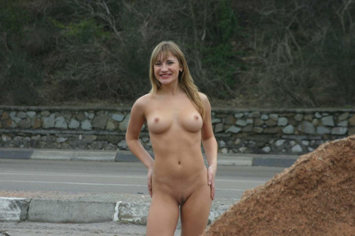 Blonde with posh boobs and hot body posing by the road