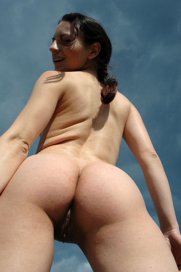 Brunette shows her fuckholes by the old church