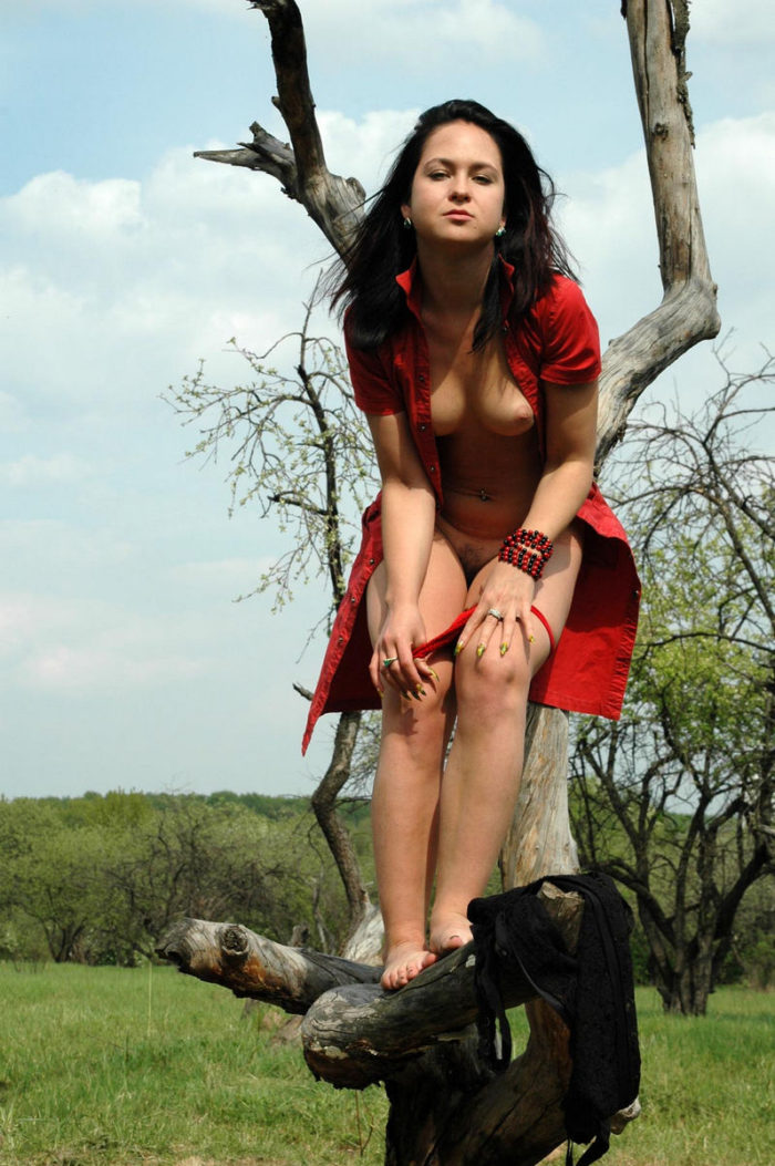 Brunette with beautiful face posing in sexy dress outdoors