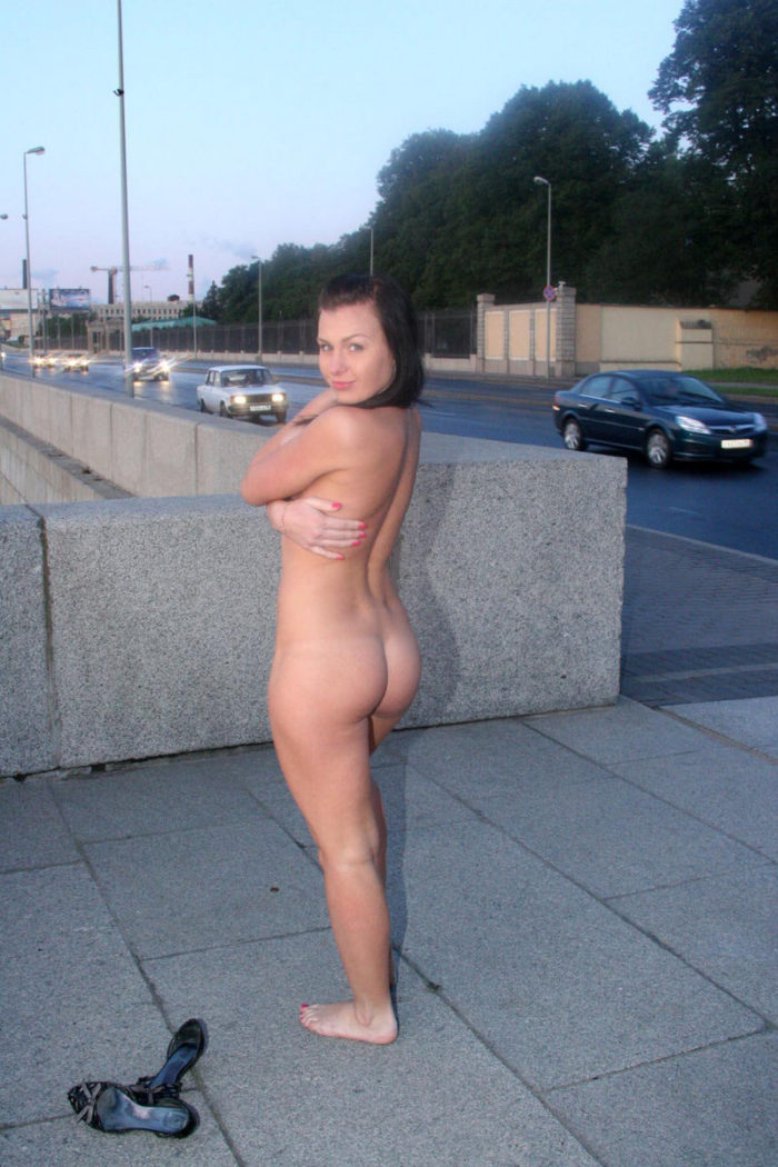 Busty brunette without clothes near busy road