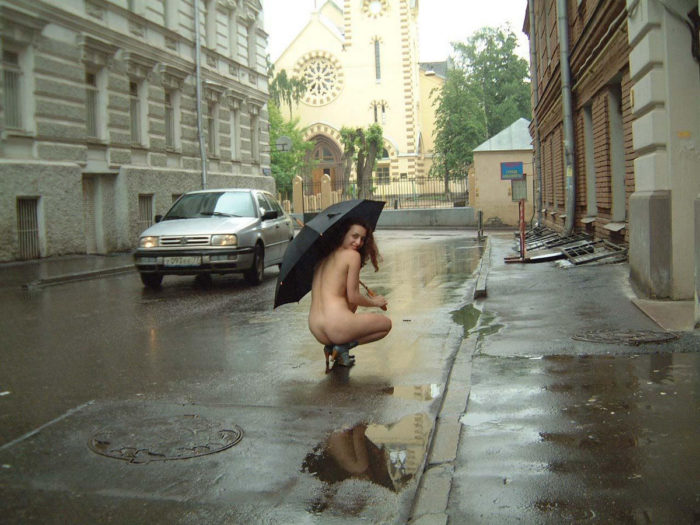 Curly girl in boots and an umbrella on a rainy street