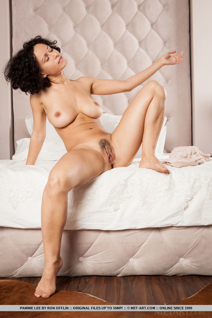 Curly-haired Pammie Lee shows off her big tits and trimmed pussy on the bed.