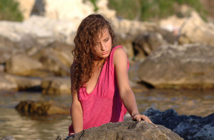 Curly-haired girl on a rocky shore