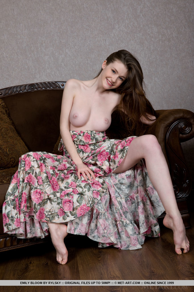 Emily Bloom shows off her creamy body and pink, smooth pussy on the sofa.