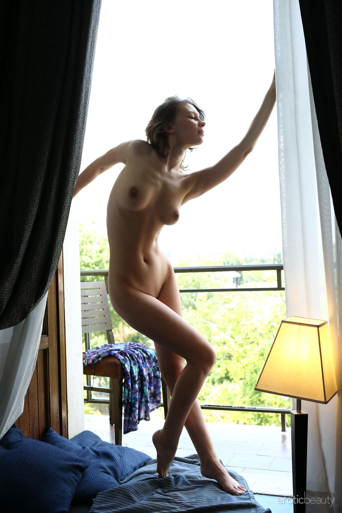Galina A bares her beautiful tits and flexible body as she poses by the door.