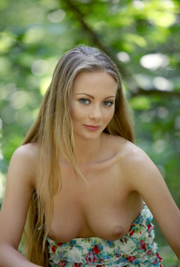 Luxurious girl undressing in a sunny forest