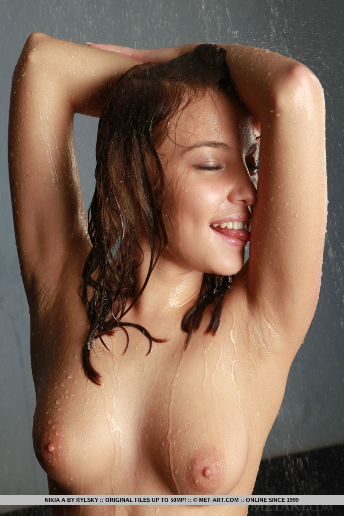 Nikia A displays her wet, nubile body and smooth pussy on the floor.