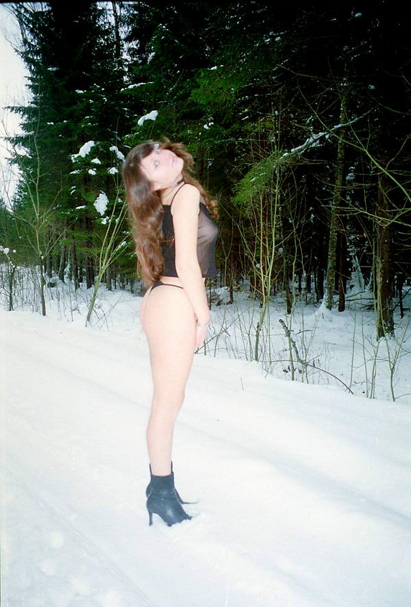 Old photos of a girl in a sexy suit in a winter forest