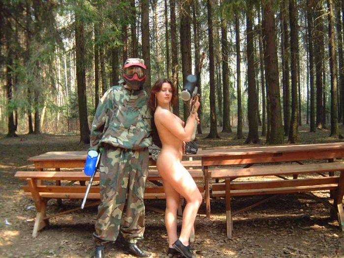 Russian girl posing with paintball gun in the forest
