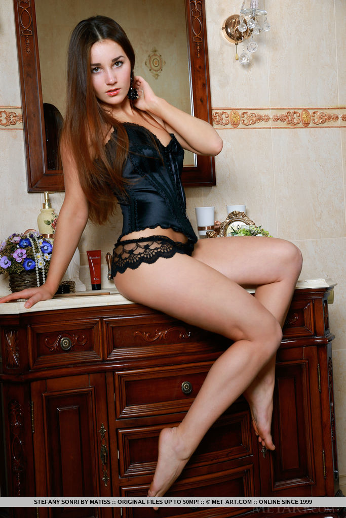 Stefany Sonri strips her sexy, black corset as she poses on top of the dresser.