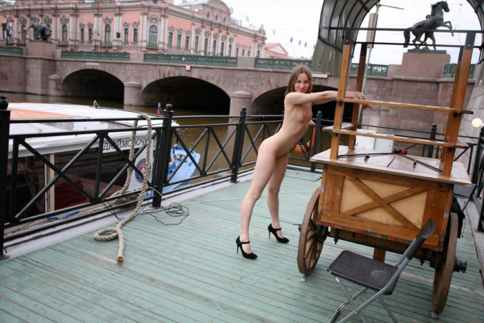 Sweet girl Irina O shows her young body by the city river