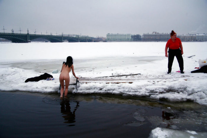 Young brunette wants to swim in an ice hole in winter