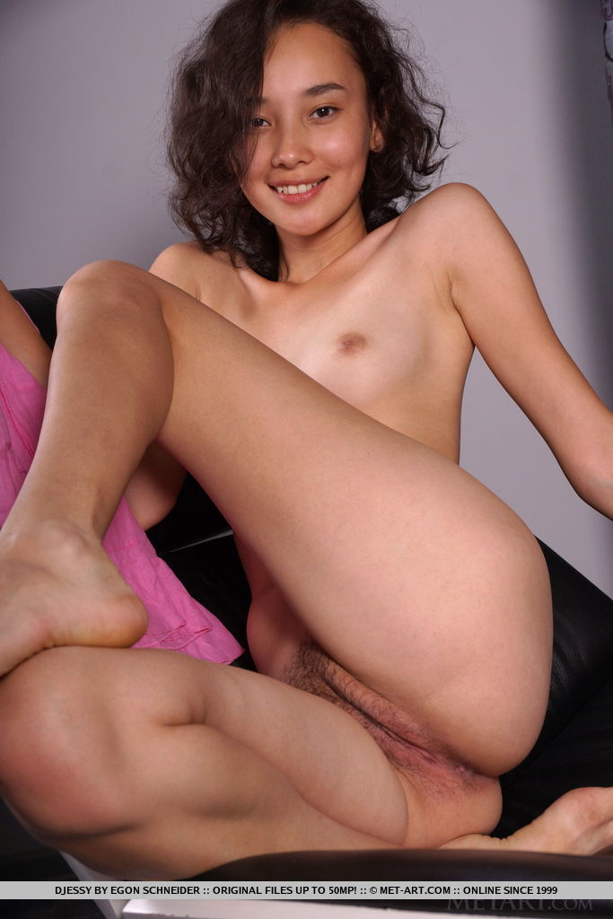 Youthful Djessy	poses on the sofa as she flaunts her hairy pussy.