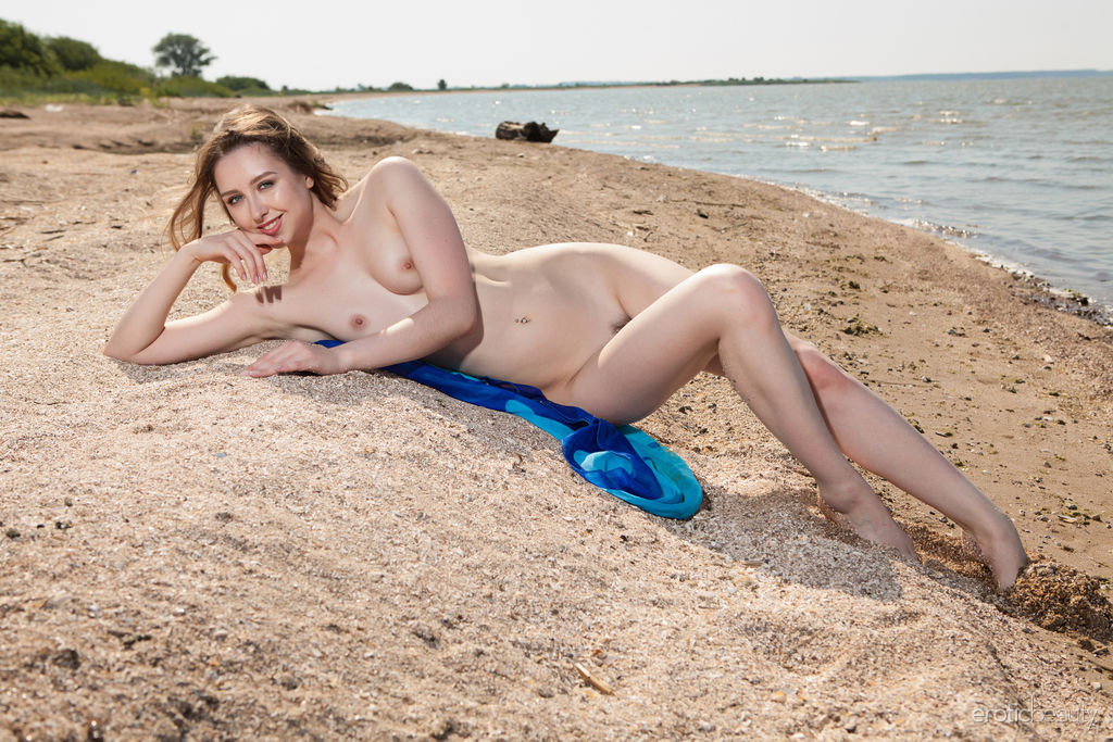 Ginger Frost flaunts her amazing physique and trimmed pussy on the beach.