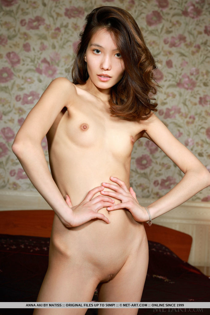 New model Anna Aki displays her petite body and small pussy on the bed.