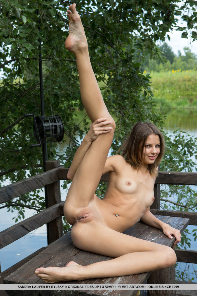 Sandra Lauver enjoys the cool breeze as she lounges naked under the tree shade by the river.