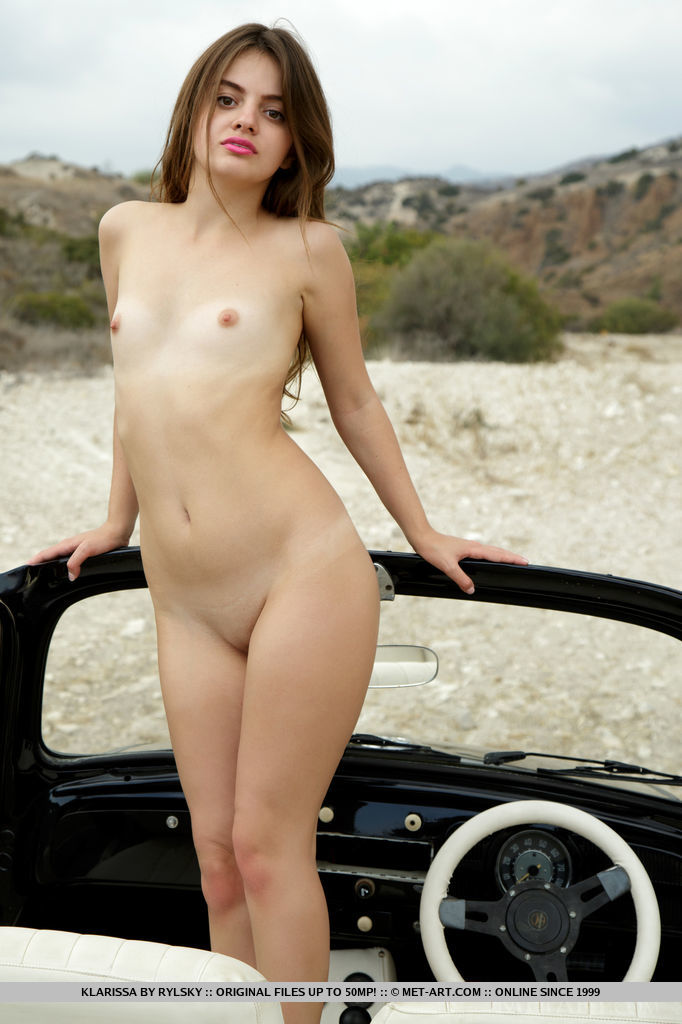 Sexy and confident, Klarissa poses with a vintage a car in the outdoor