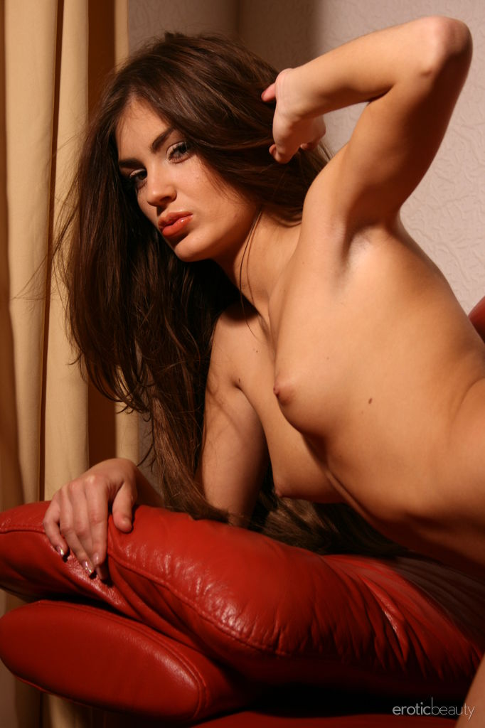 Sveta F shows off her sexy, tight body as she poses on the red couch.