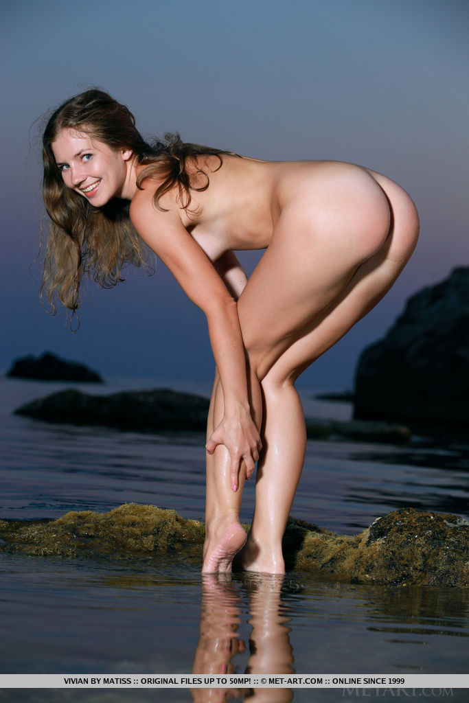 Vivian strips outdoors baring her nubile body at the beach.