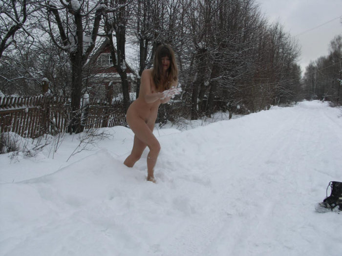 A girl takes off her boots in a snow-covered village