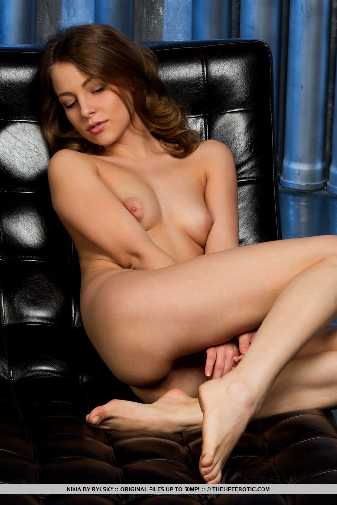 Alluring Nikia poses on the chair baring her manicured pussy.