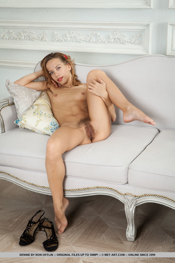 Dennie spread her legs wide open as she flaunts her delectable unshaven labia with a   warm, engaging smile on the sofa.