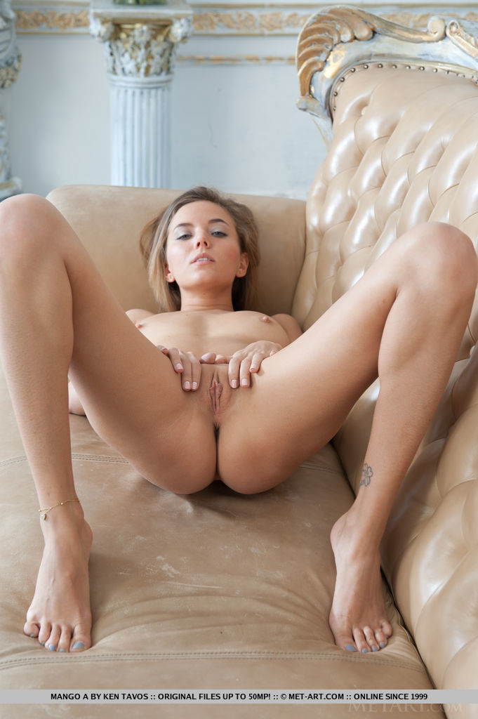 Mango A bares her erect nipples and smooth pussy on the sofa.