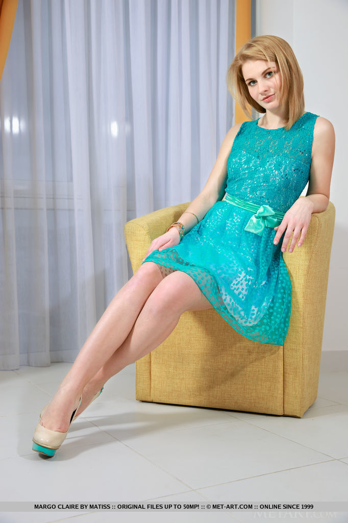 Margo Claire strips off her aqua blue dress and starts posing her smooth, naked body on the sofa
