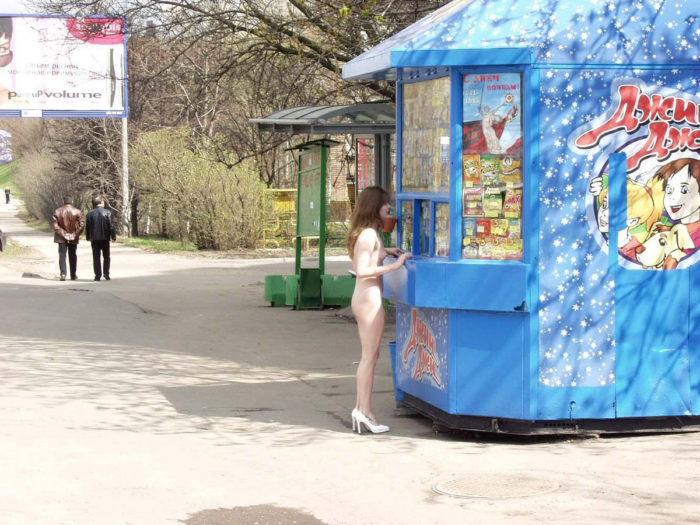 Naked girl buys some things in the kiosk