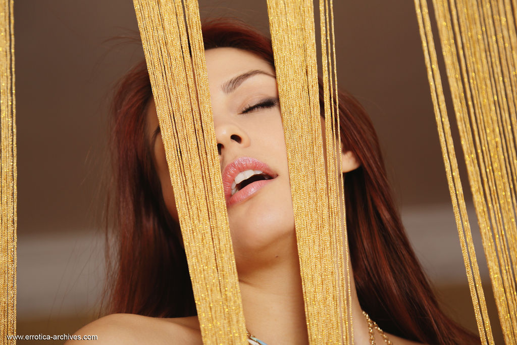 Redhead Alise Moreno bares her smooth, delectable pussy in front of the camera.