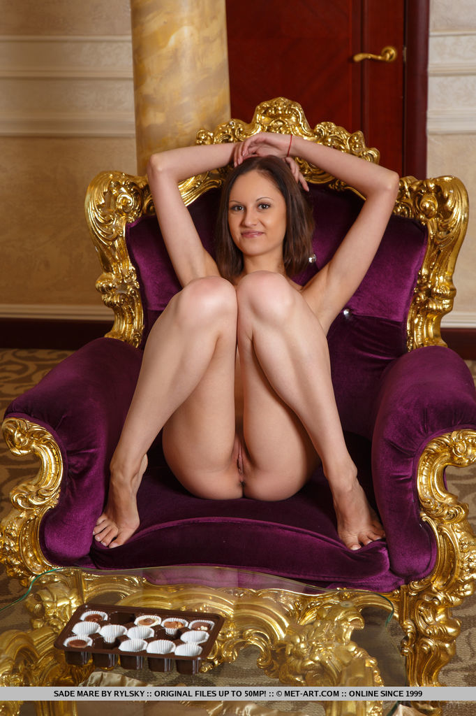 Sade Mare displays her petite body and sweet pussy on the chair.