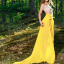 Vivian strips her long, yellow dress baring her tight body and smooth pussy in the forest.
