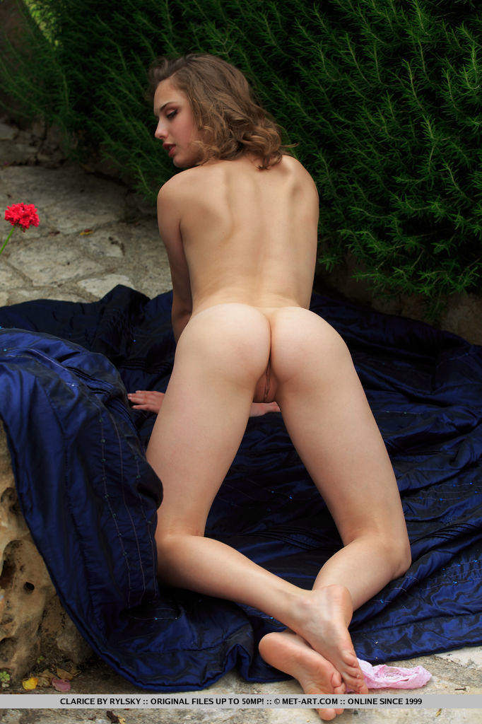 Clarice lays on the floor outdoors as she flaunts her tight body.