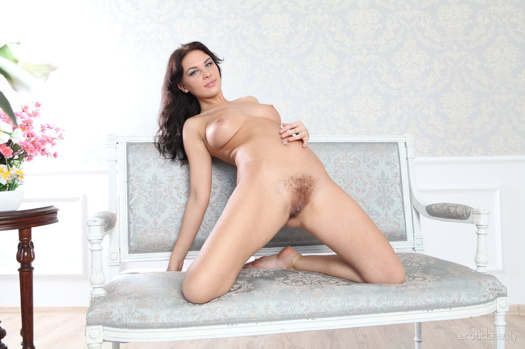 Galina A takes off her white top and flaunts her curvy body with large puffy breasts on the white sofa.