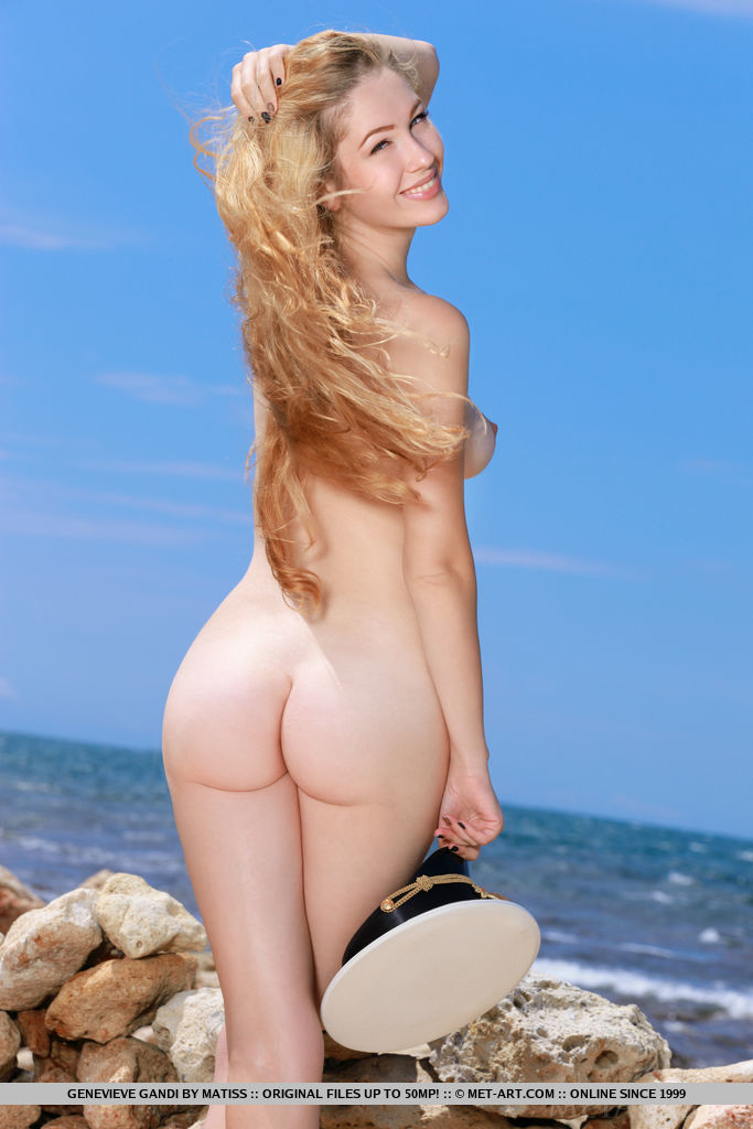 Genevieve Gandi poses by the rocky beach baring her pink, creamy pussy.