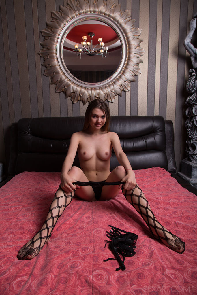 Georgia posing seductively in bed, wearing fishnet and matching lace panty