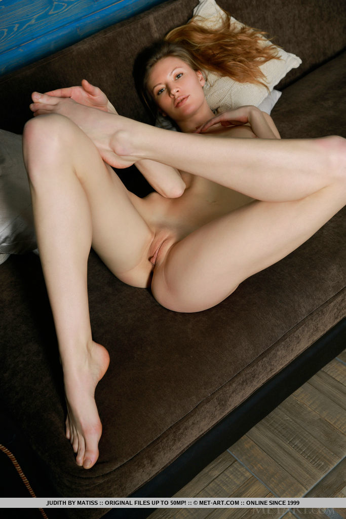 Judith bares her sexy, tight body and delectable pussy on the sofa.