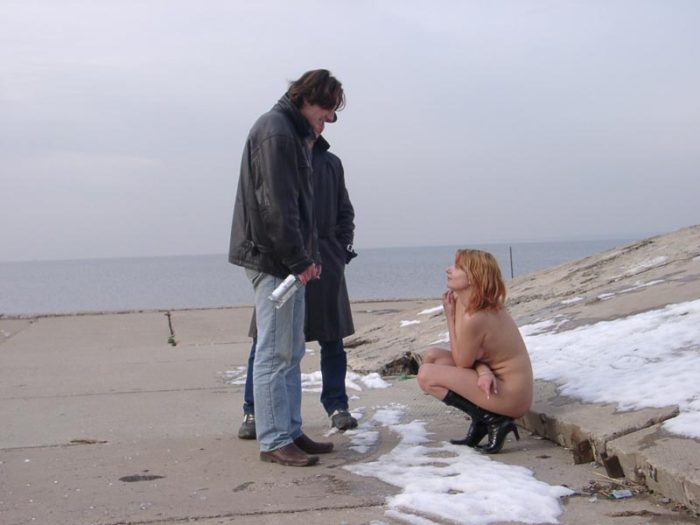 Naked girl drinks vodka with strangers on the waterfront