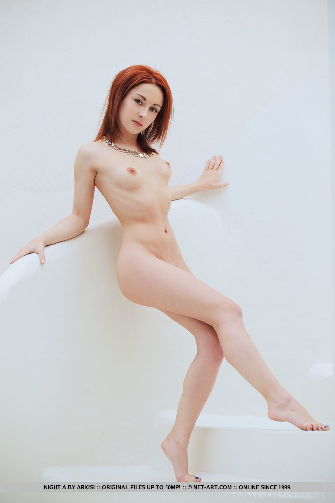 Night A's lean body, bright red hair, and smooth fair skin stands out against the monotonous white set.