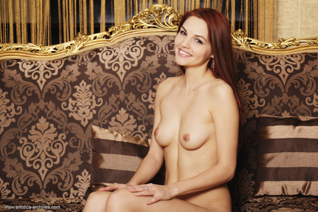 Redhead Alise Moreno flaunts her beautiful tits and delectable pussy on the couch.