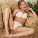 Seductive and confident, Lucy Heart sprawls on the sofa as she slowly takes off her lingerie