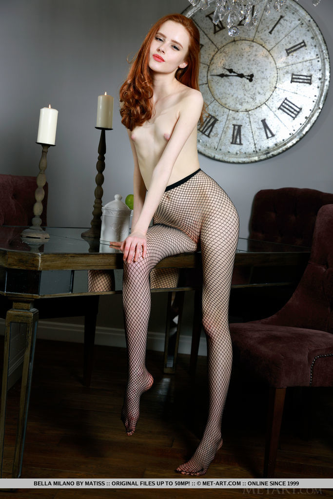 Sultry redhead Bella Milano wearing nothing but a black fishnet stockings