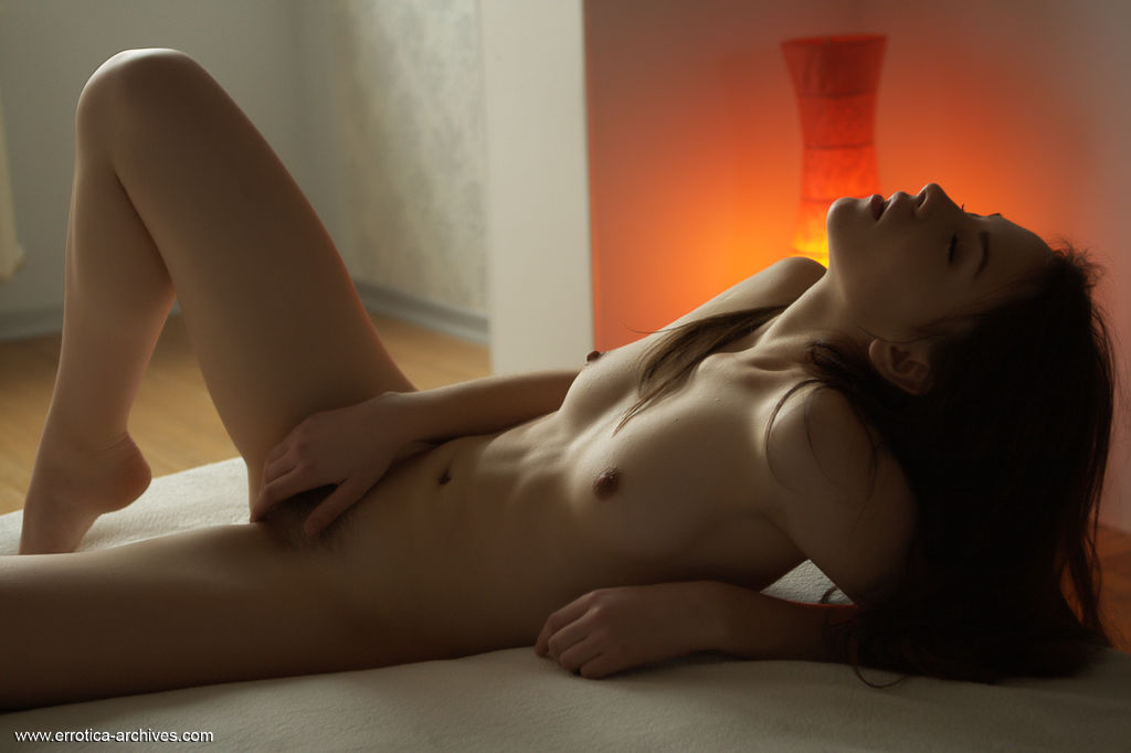 Una Piccola lays on the bed as she sensually touch her body.