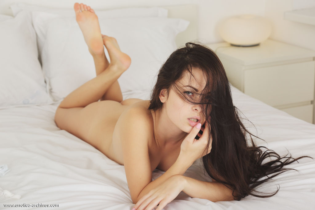Amelie B lounges on top of the bed and showcases her smooth, shaved pussy